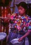 Mayan girl weighing beans Chichicastenango market Guatemala