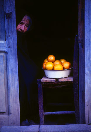 Selling oranges in doorway,