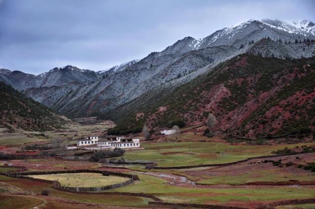 Tibet, farm with fresh snow in mountains near Markham
