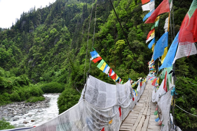 Tibet, bridge over the Parlung Tsangpo River draped with prayer flags near Bakhar Monastery.