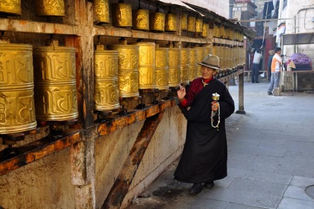 Tibet, spinning prayer wheels along the Barkhor circuit kora, Lhasa