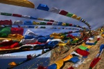 Tibet - prayer flags blowing in the strong wind above Nam-tso Lake.