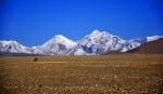 A lone horseman crosses the barren Tibetan Plateau at 4,600 meters between Shishapangma and Paiku Lake, Tibet
